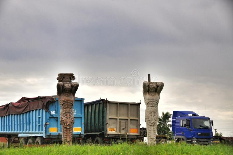 Two statues and a truck. The unusual location of the statues of Hercules in the field on the background of the truck stock images