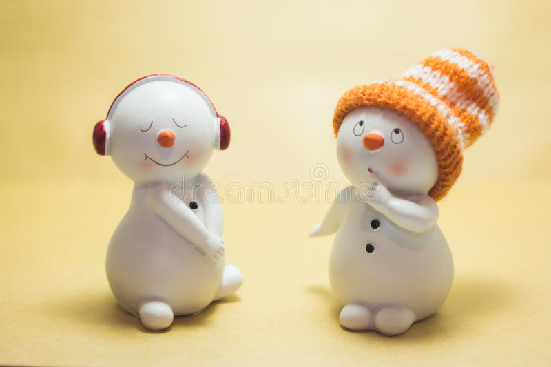 Two statuette snowmen. With a cap and headphones on beige background stock photo