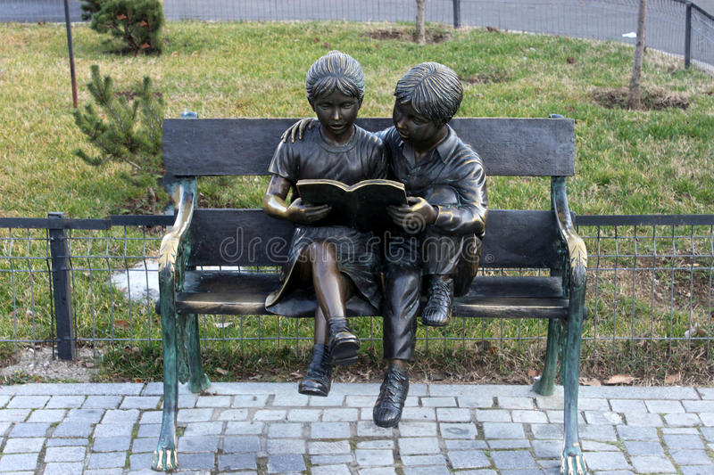 Two statuettes, standing reading on a park bench stock image