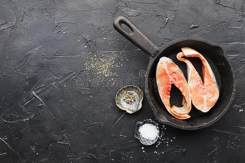 Two steaks of pink salmon of the salmon family, wild sea fish. Healthy food for the whole family. Top view. On a dark. Background in a cast iron skillet before stock photo