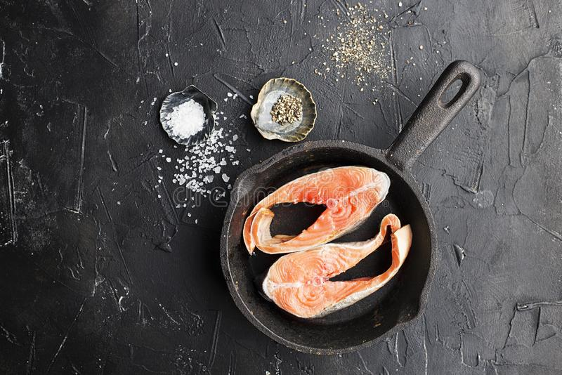 Two steaks of pink salmon of the salmon family, wild sea fish. Healthy food for the whole family. Top view. On a dark. Background in a cast iron skillet before royalty free stock images