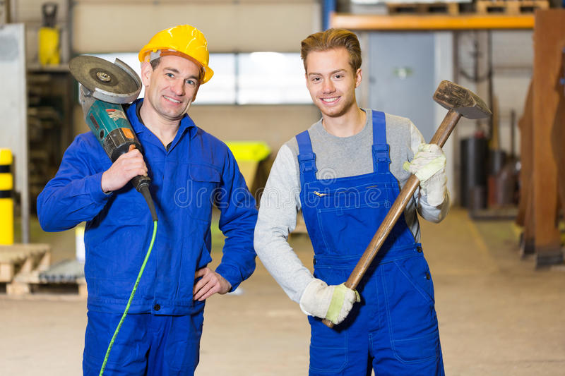 Two steel construction workers posing with angle grinder and ham stock photography