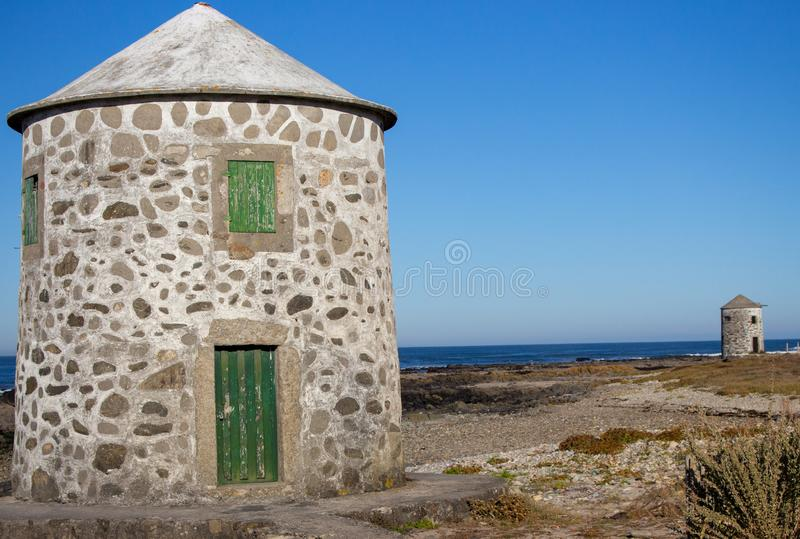 Two stone abandoned lighthouses on atlantic ocean coast. Medieval european architecture. Ancient navigation concept. stock images