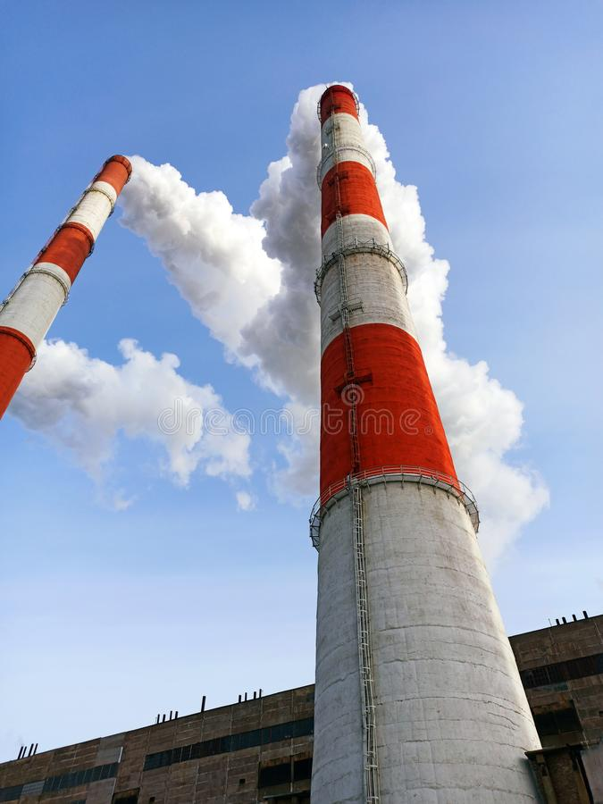Two stone pipes of a power plant releasing steam from generating electricity against a blue sky stock images