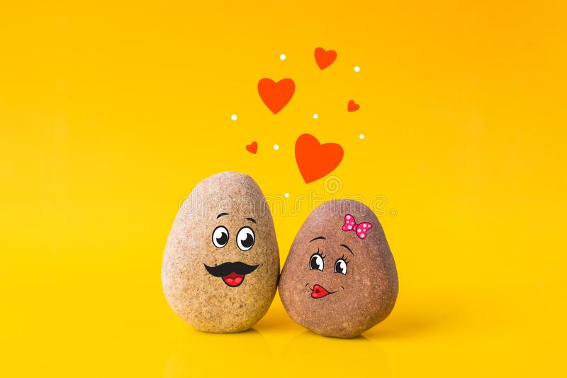 Two stones with drawn funny faces in love royalty free stock photo