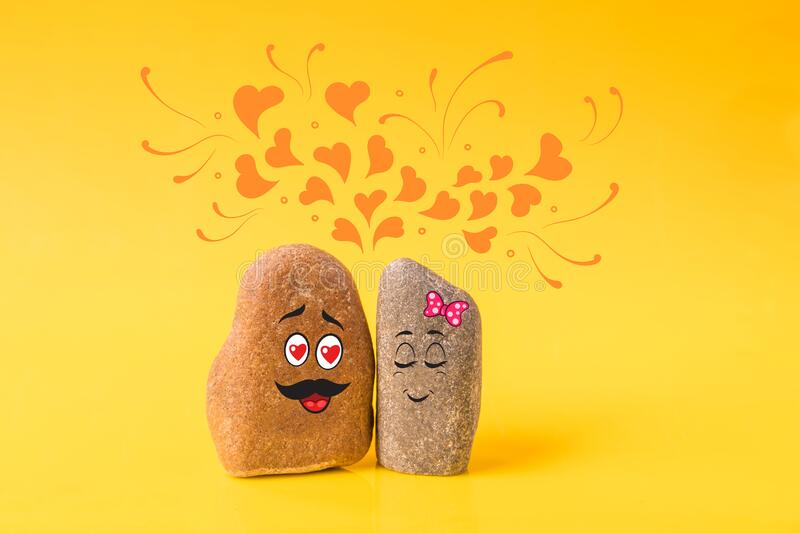 Two stones with drawn funny faces in love stock image