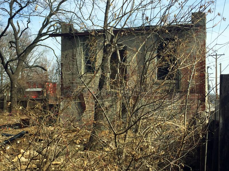 Two story abandoned business back view overgrown stock photography