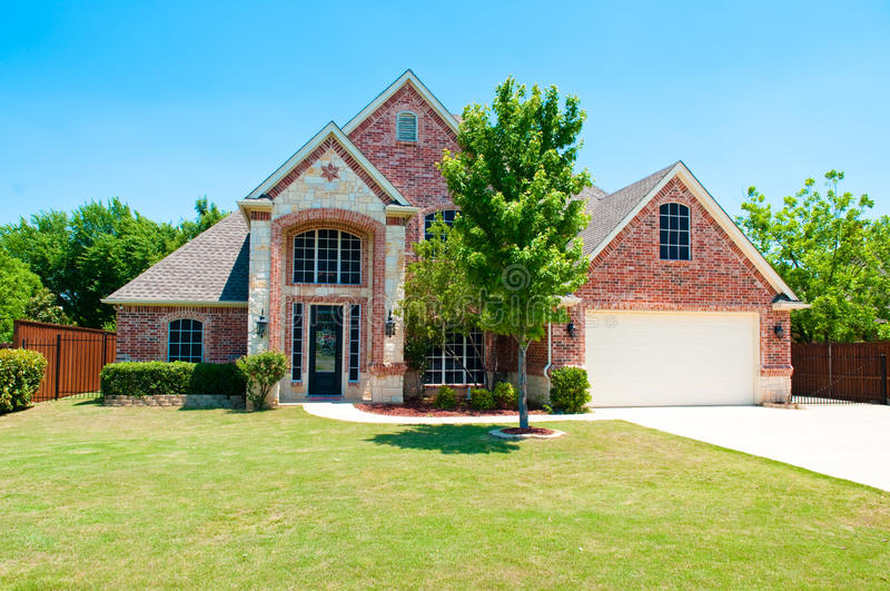 Two story brick home with the garage in the front. stock images