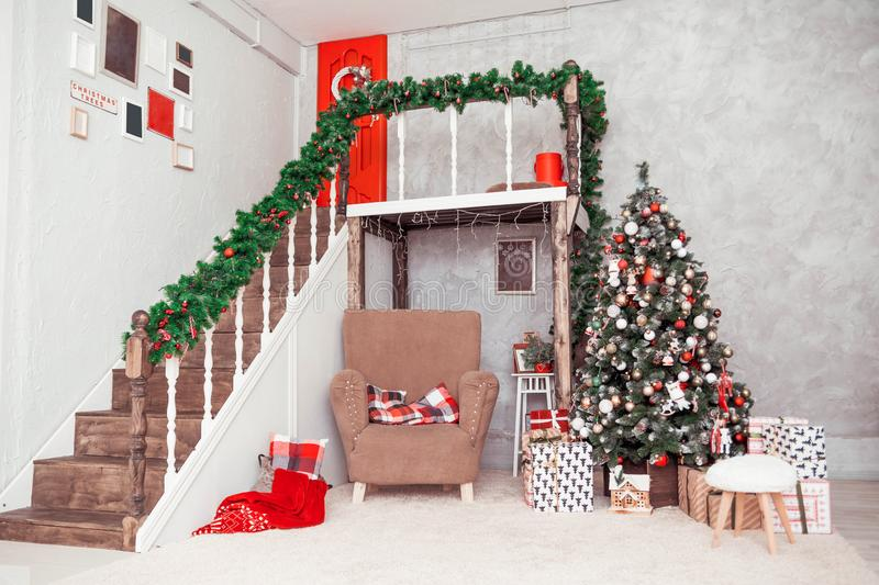 Two-story room in a classic New Year style with a large chair and a Christmas tree royalty free stock image