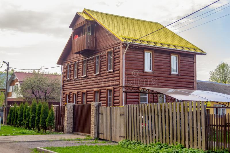 A two-story wooden brown log house, with an attic and a yellow tiled roof. stock photos