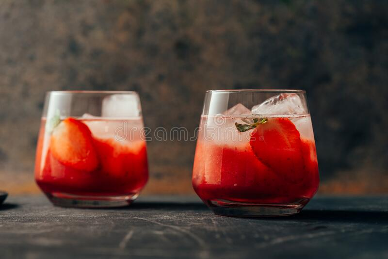 Two strawberry cocktail with ice on dark background stock photo