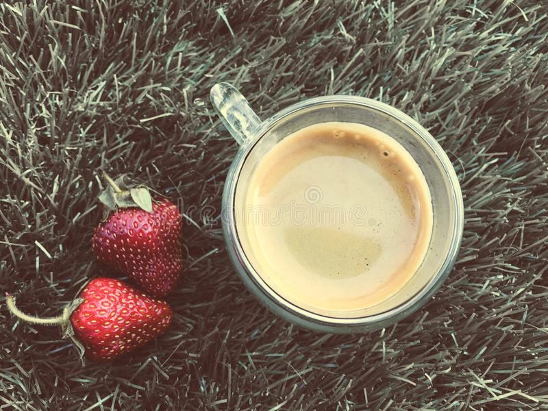 Two strawberrys on the grass with cup of coffee royalty free stock photo