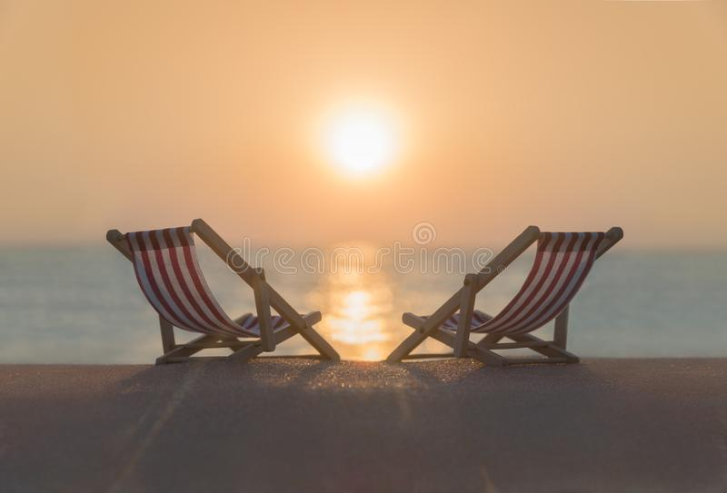 Two striped red-white sunbeds at sandy tropical sunset ocean beach. royalty free stock photos