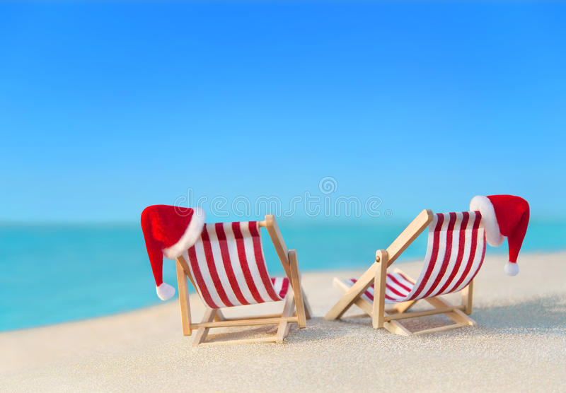 Two striped sunloungers with Christmas Santa hats at ocean beach royalty free stock images