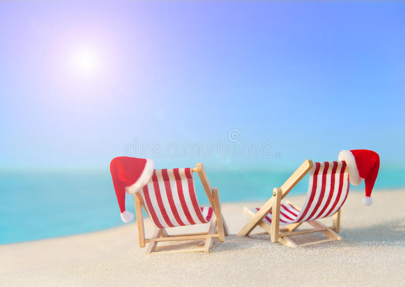 Two striped sunloungers with Christmas Santa hats at ocean sunset beach. Two striped red-white sunloungers with Christmas Santa hats for romantic couple at ocean stock photo