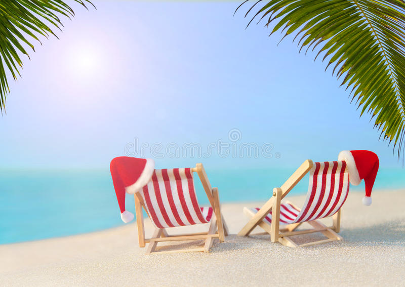 Two striped sunloungers with Christmas Santa hats at ocean sunset palm beach stock images