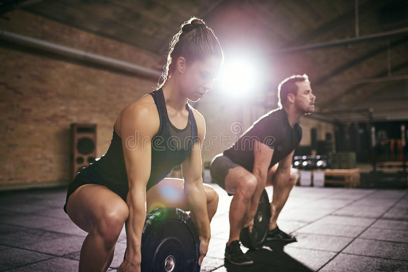 Two strong people training with weight disks royalty free stock photos