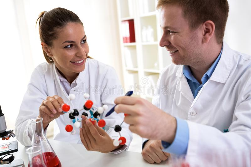 Two students of chemistry looking at molecular model and making. New formula at laboratory stock image