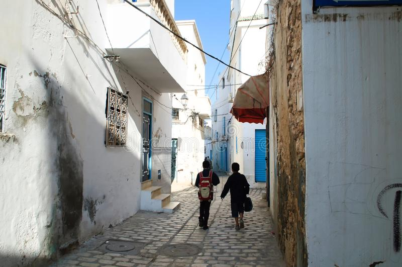 Two students go to school on the street of the old town of Sousse royalty free stock photography
