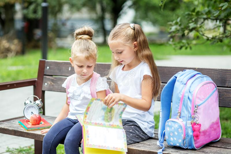 Two students read books on a bench. The concept of school, study, education, friendship, childhood. Two students read books on a bench. The concept of school royalty free stock photos