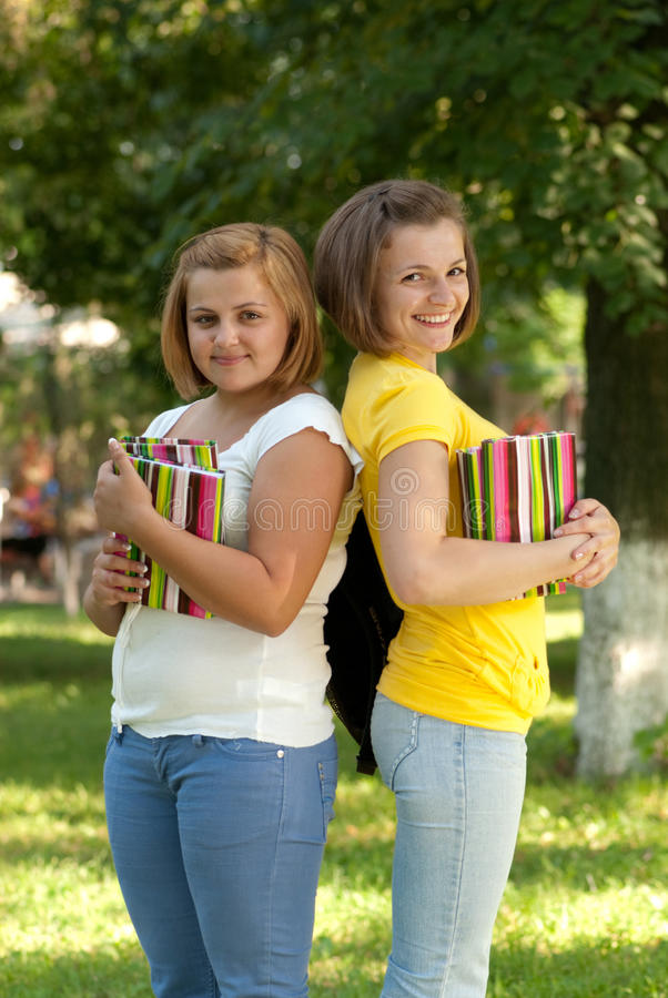 Two students. Two smiling female students in campus park stock photography