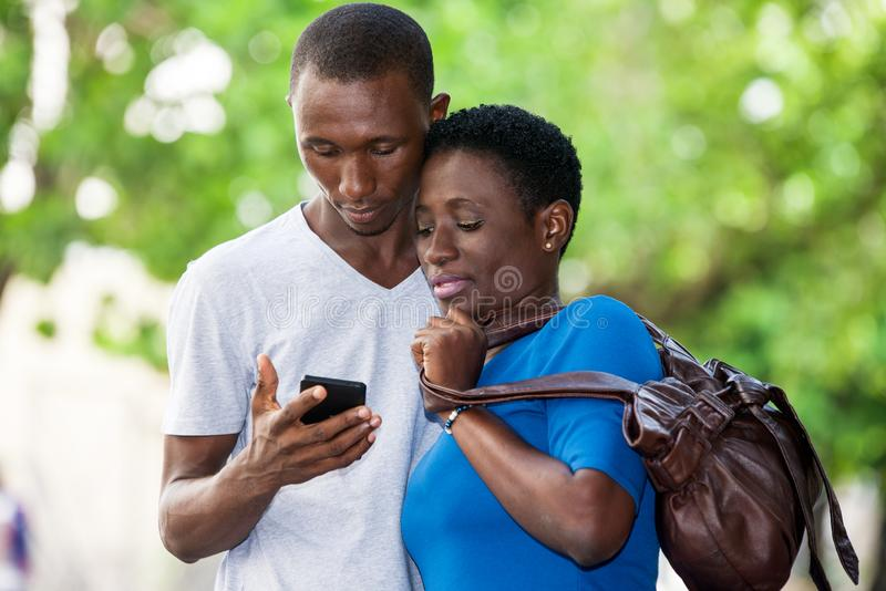 Portrait of young people. Two students standing in park and look at mobile phone while smiling stock photo