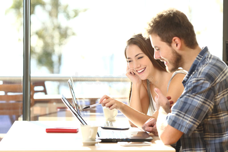 Two students studying in a coffee shop stock image