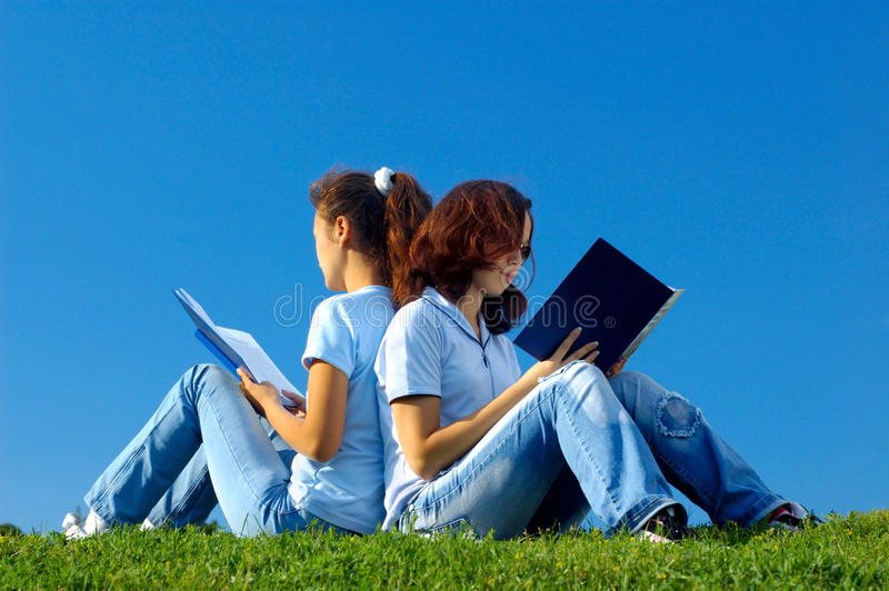 Two students studying in the nature. Two girls students sitting on grass studying in the nature reading books stock photography