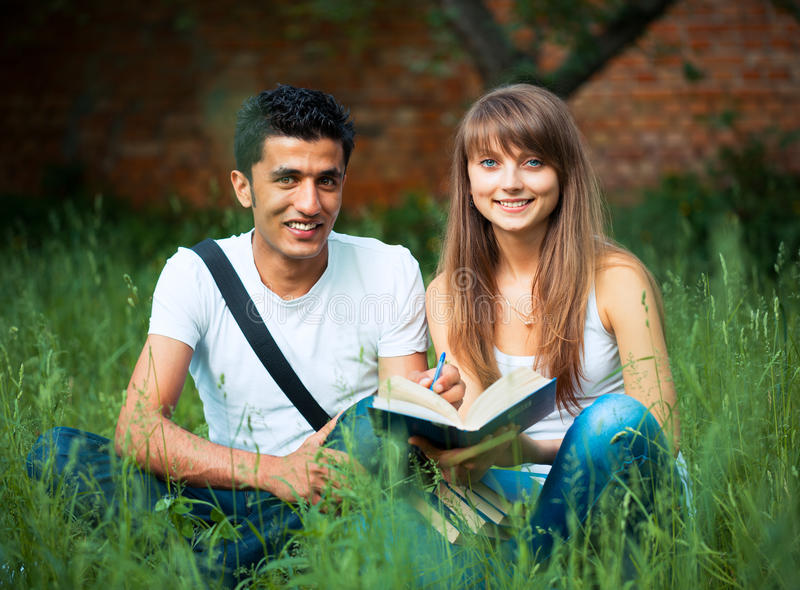 Two students studying in park on grass with book outdoors. Two students guy and girl studying in park on grass with book outdoors stock photos