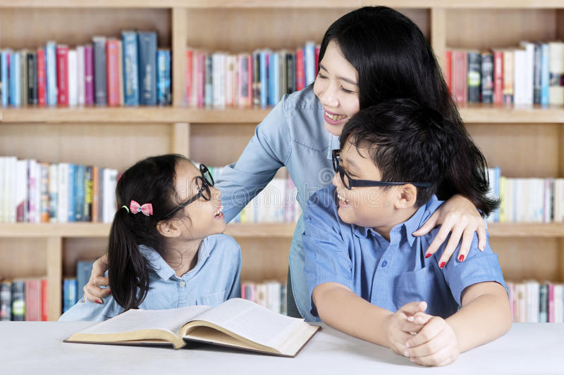 Two students talking with her teacher stock photography