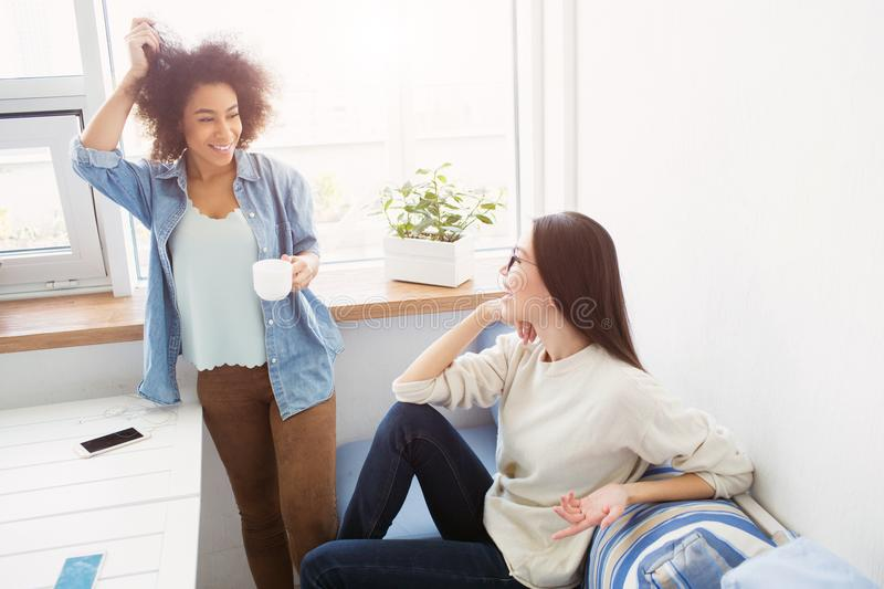 Two students are talking to each other. Afro american girl is standing near window and touching her hair while european stock image