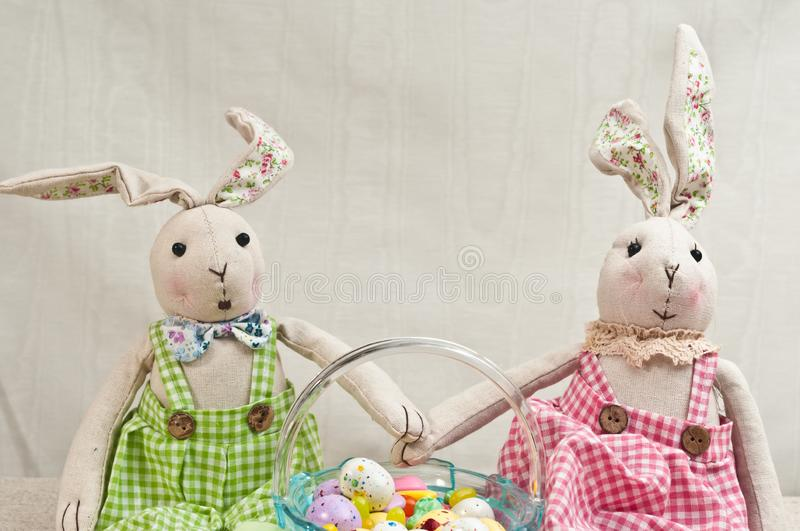Two, stuffed, baby rabbits and easter basket of candy royalty free stock images