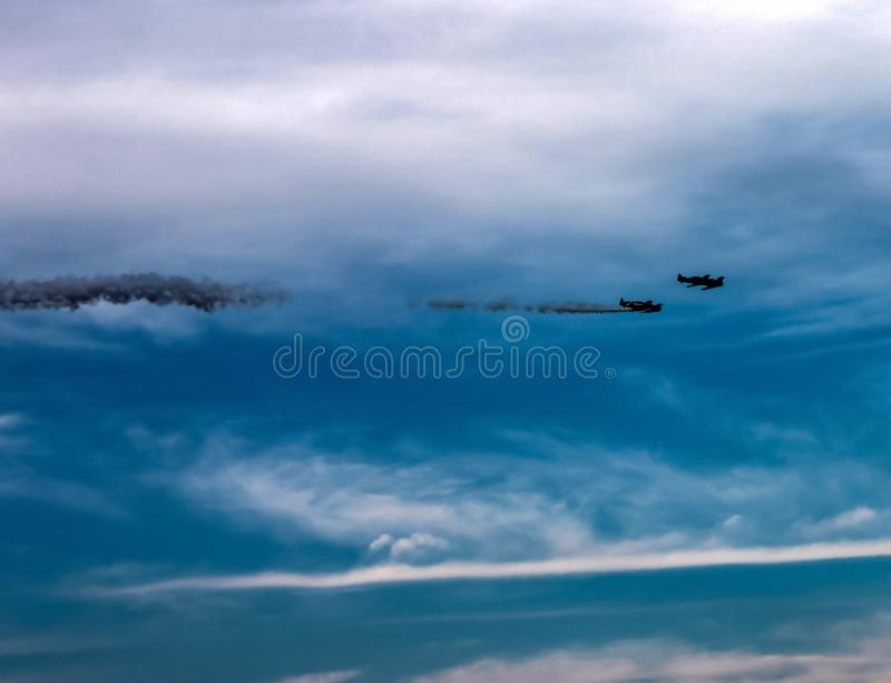 Two stunt planes in the sky - one with smoke billowing out royalty free stock images
