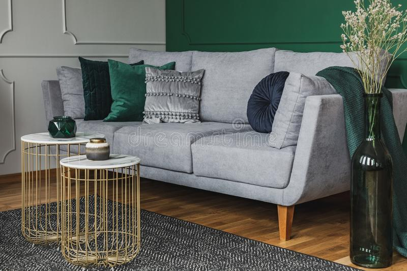 Two stylish small coffee tables with marble tops in front of elegant grey couch with emerald pillows. Two stylish small coffee tables with marble tops in front royalty free stock photography