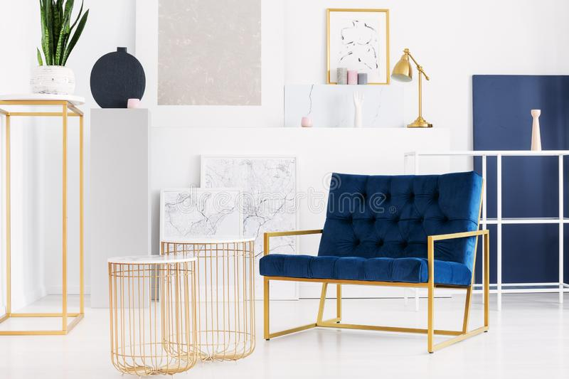 Two stylish tables next to petrol blue armchair in bright living room interior of modern apartment royalty free stock photo