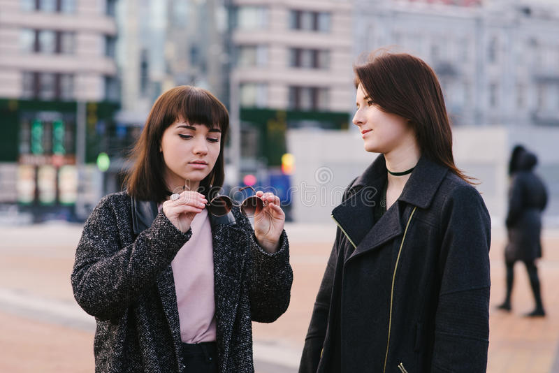 Two stylish young girlfriends wearing casual walk around the city and communicate. one girl holding sunglasses stock image