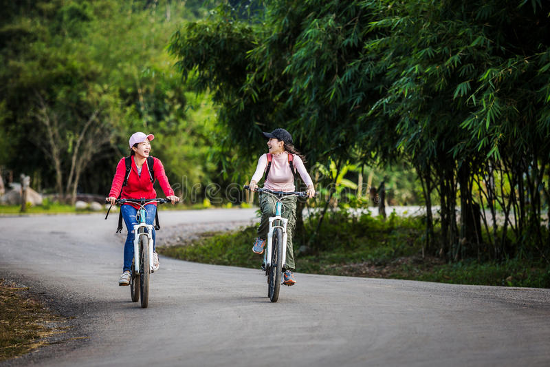 Two stylish young girls cycling along the road`s best friend enj royalty free stock photos