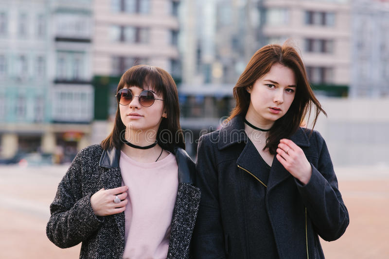 Two stylish young women models dressed in casual pose against the backdrop of the city on a sunny day spring day royalty free stock photography