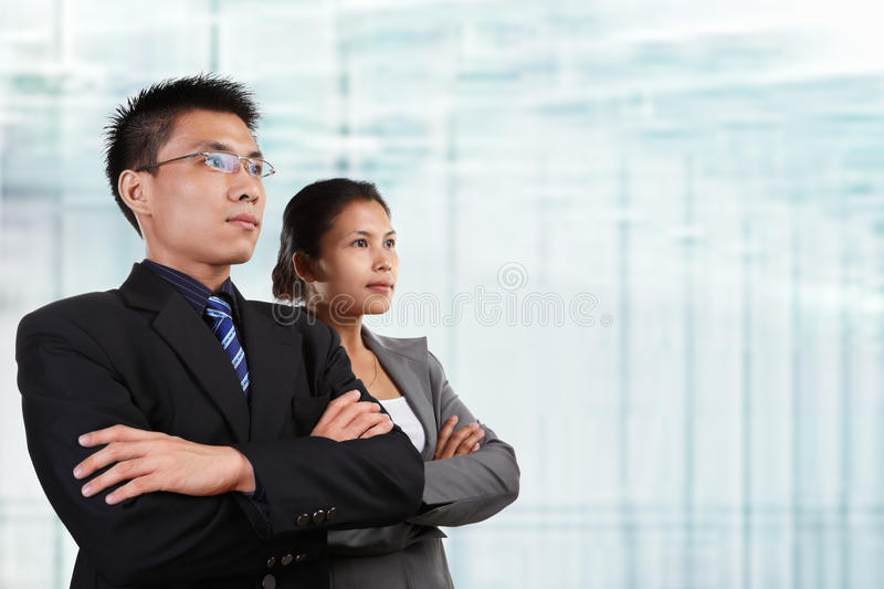 Two successful Asian business people. Looking at empty space, with blur glass windows as background royalty free stock photo