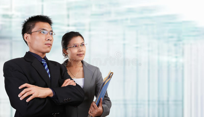 Two successful Asian business people. Chinese businessman with his secretary looking to empty space, with blur glass window as background stock photo