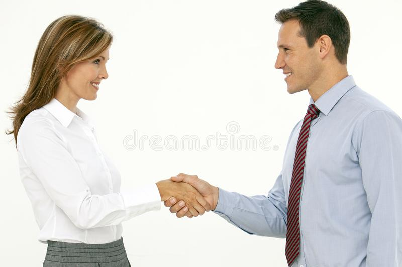 Two successful beautiful corporate business people shaking hands royalty free stock images