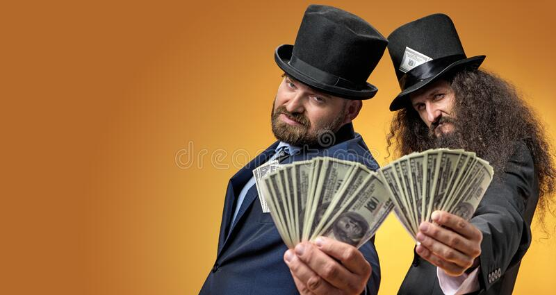Two successful businessmen holding a bunch of dollars royalty free stock photography