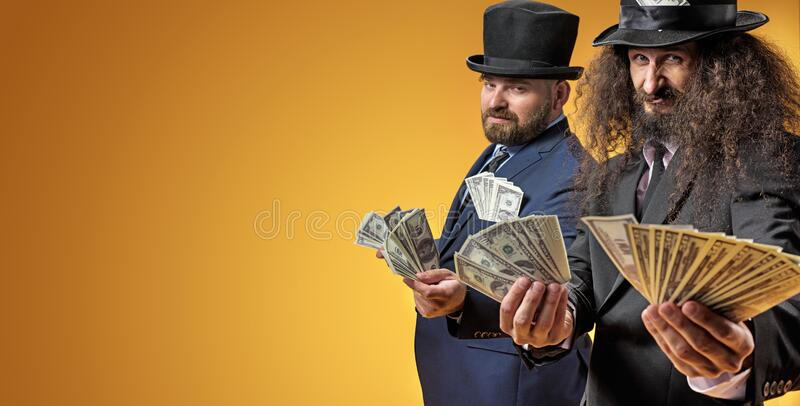 Two successful businessmen holding a bunch of dollars royalty free stock image
