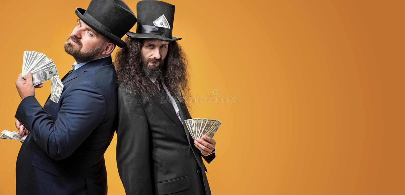 Two successful businessmen holding a bunch of dollars stock photography