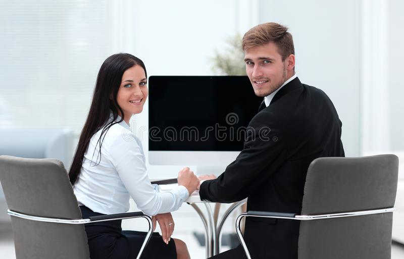 Two successful employee sitting behind a Desk. And looking at camera. photo with copy space stock image