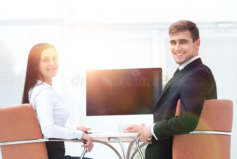 Two successful employee sitting behind a Desk. And looking at camera. photo with copy space royalty free stock image