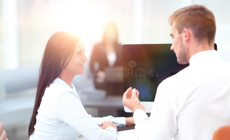 Two successful employee talking sitting behind a Desk. Photo with copy space royalty free stock photography