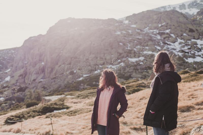 Two successful hiker woman friends enjoy the view on mountain peak. Happy backpackers in nature stock photo