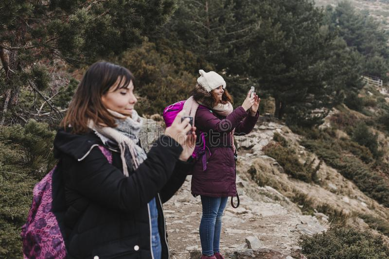 Two successful hiker woman friends enjoy the view on mountain peak. Happy backpackers in nature taking pictures with mobile phone royalty free stock image