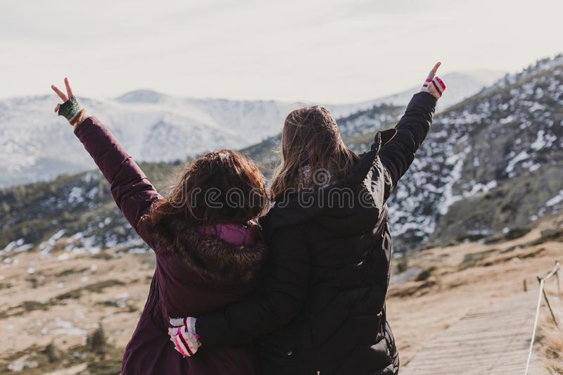 Two successful hiker woman friends enjoy the view on mountain peak at sunset. happy women in nature stock photos